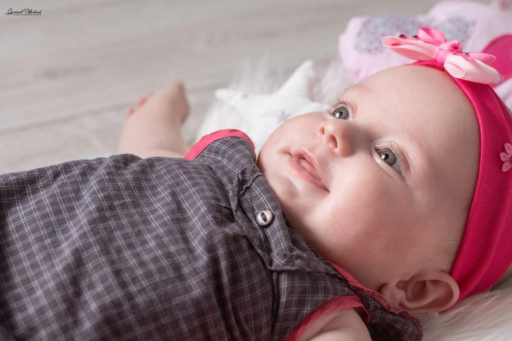 photo de bebe en studio photo avec un bandeau rose