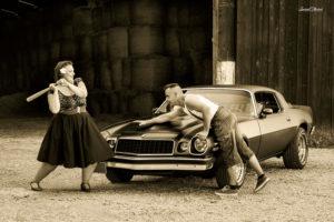 un couple avec une femme qui a une batte et une ford camaro