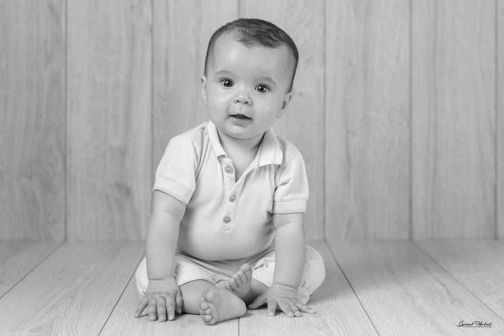 enfant assis les main au sol qui nous observe