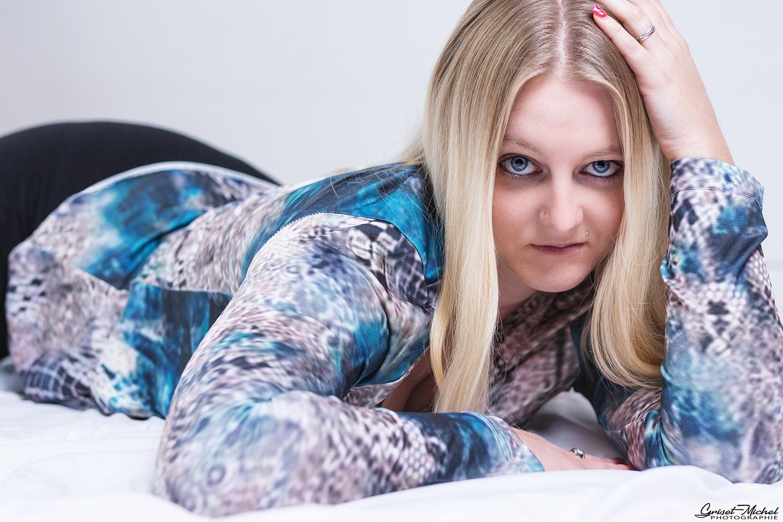femme blonde allongee avec un regard puissant qui se tiens la tete