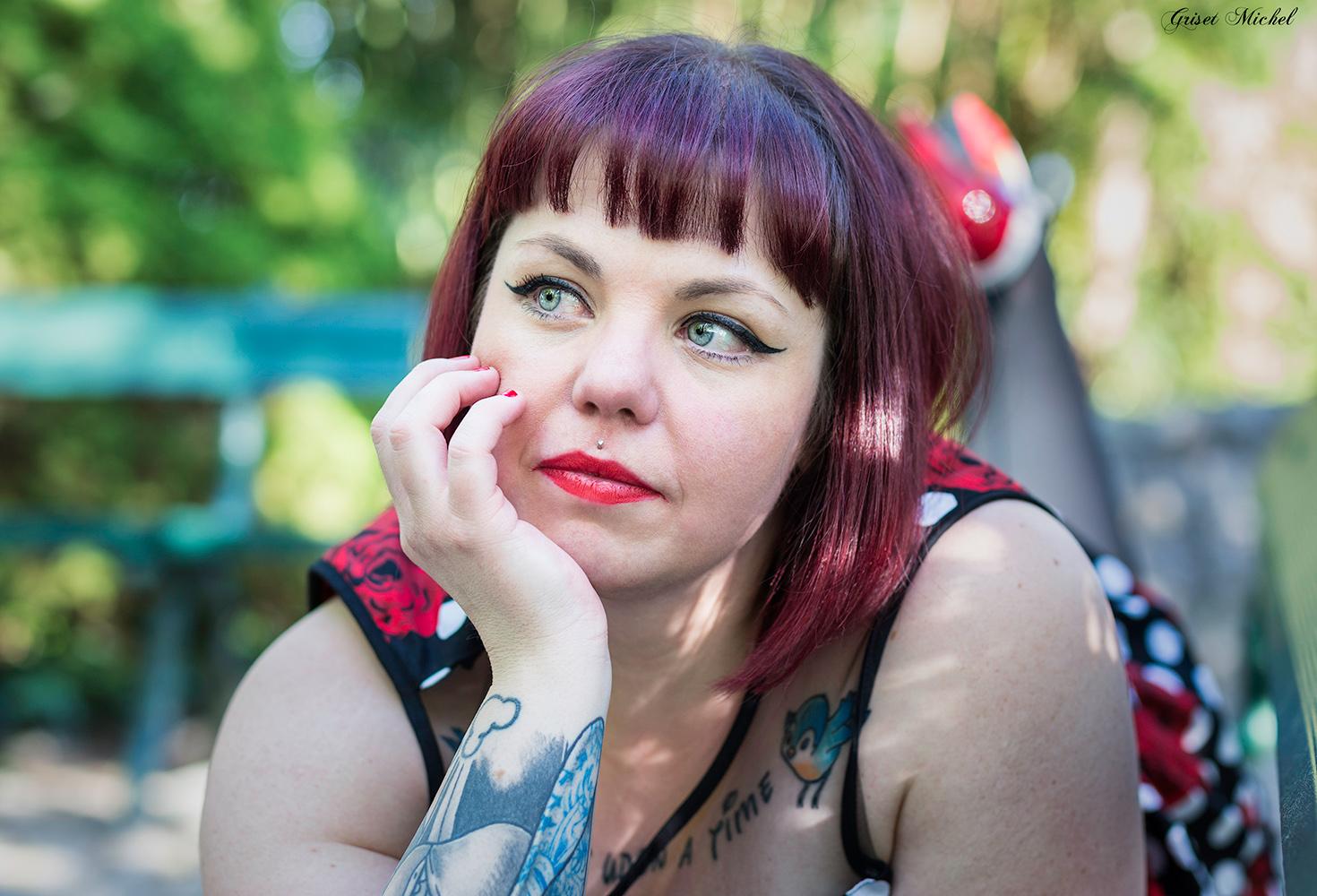femme pin up allongee sur un banc la main sur sa joue avec un beau rouge a levre et des tatouages