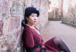 une femme assis contre un mur avec des gants et un chapeau