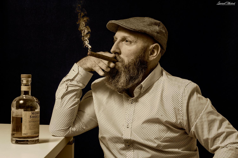 homme avec un cigare et une boutille de rhum et un beret