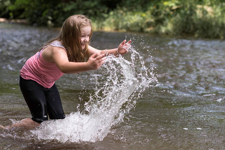 une jeune fille qui joue avec l'eau