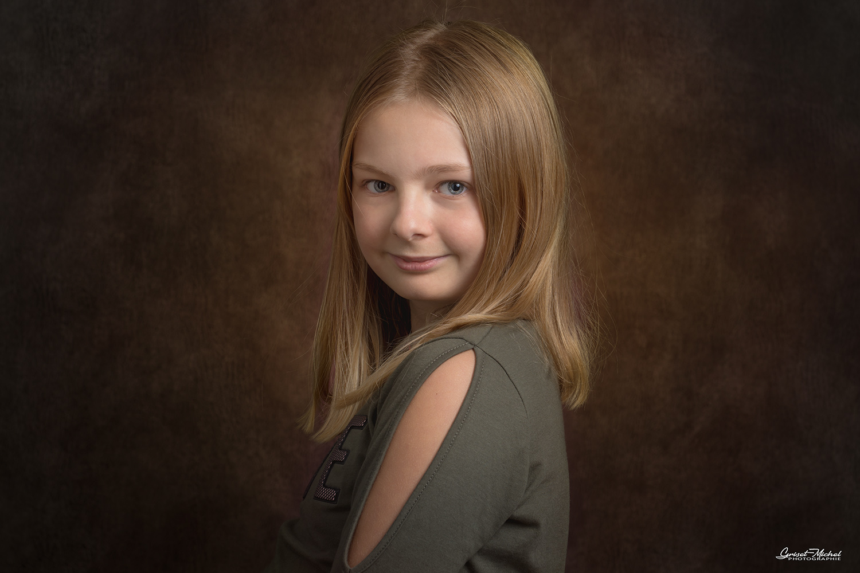 petite fille blonde avec un pull kaki sur un fond de studio rouge