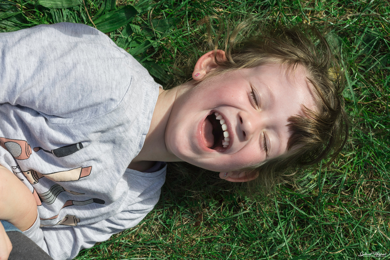 petite fille qui rigole dans l'herbe
