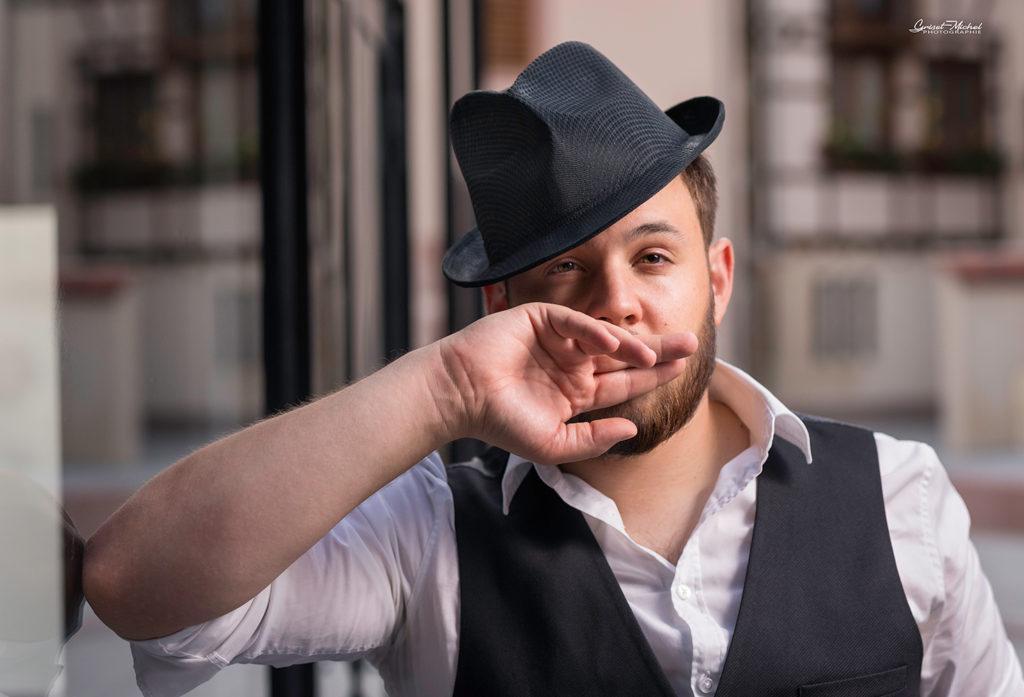 shooting homme avec un chapeau le coude sur une vitre