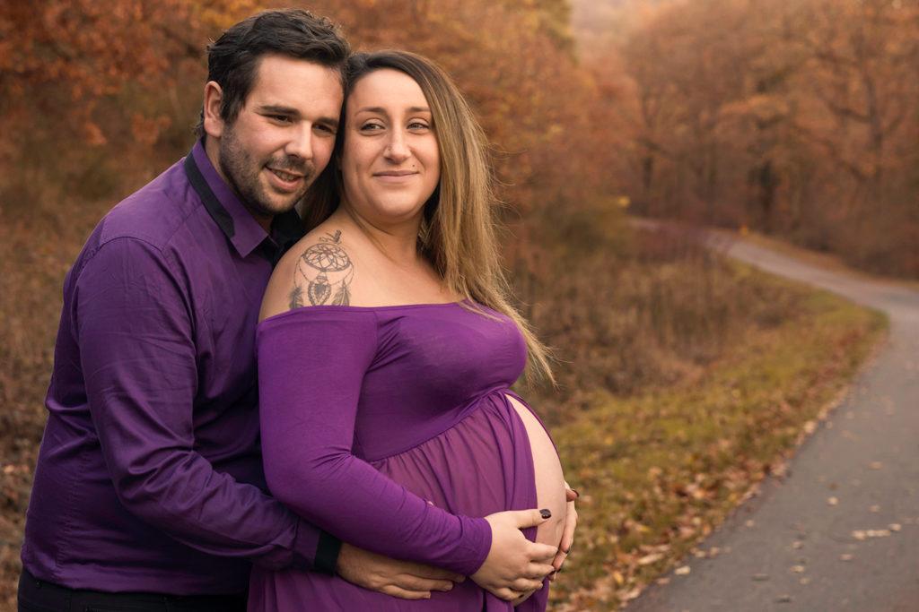 une femme enceinte fait un calin a son mari dans un decor automnal