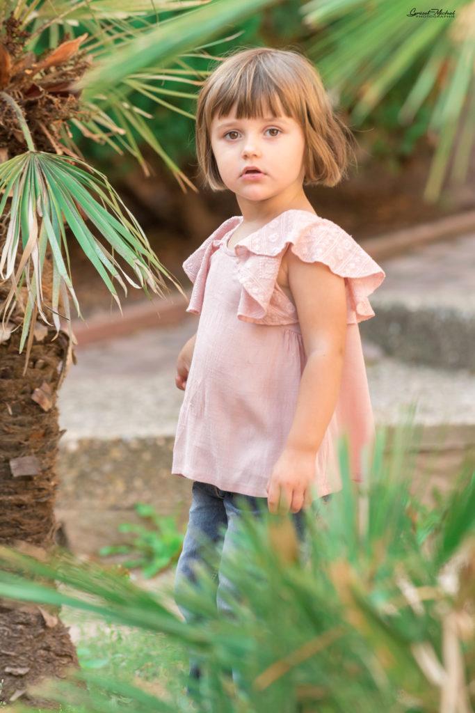 une petite fille au milieu des palmiers avec un t shirt rose