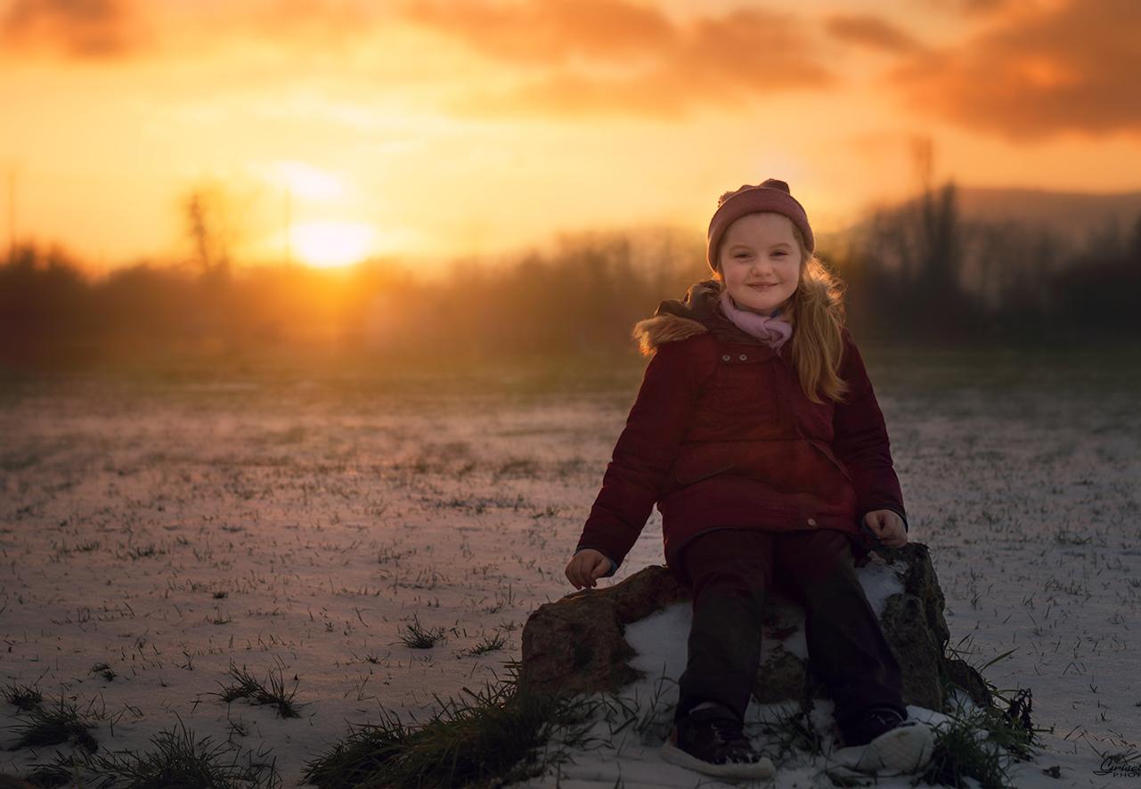 une ptite fille dans la neige avec un super coucher du soleil