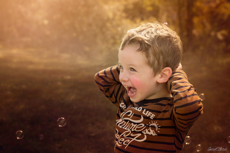 un petit garcon qui joue avec des bulles par temps automnal