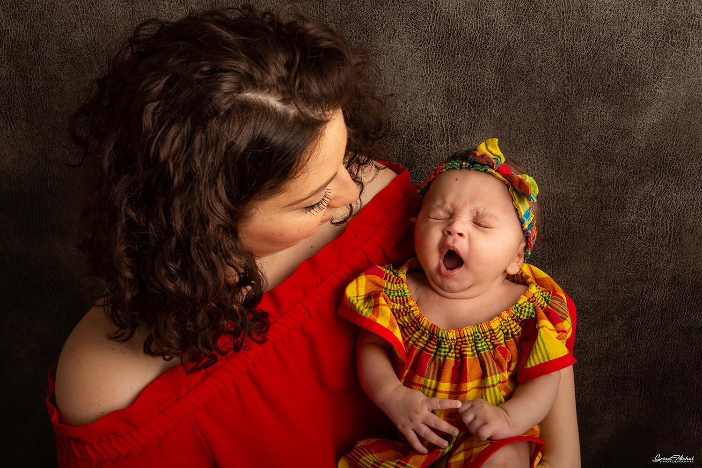 une maman tiens sa fille dans ses bras qui baille au meme moment