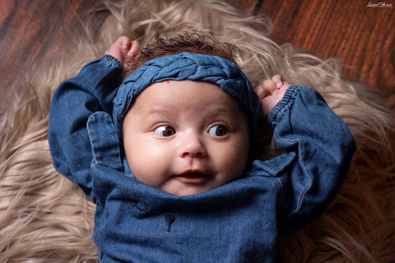 une petite fille allongee sur un tapis marron habille en bleu en studio dans le bas rhin