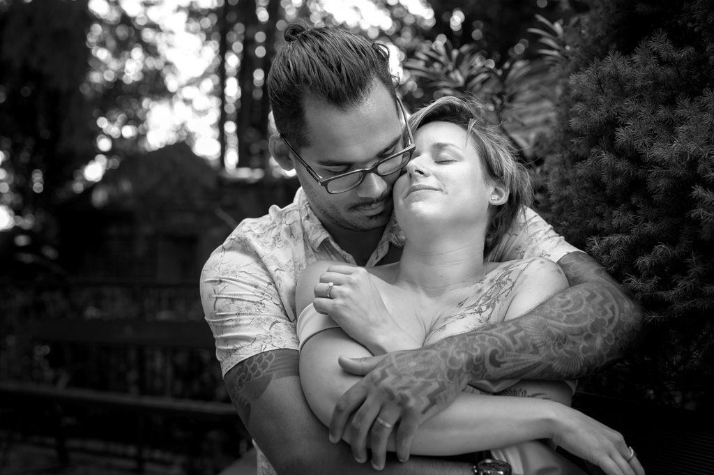 photo dun couple en noir et blanc qui se font des calins de tendresses sur un banc