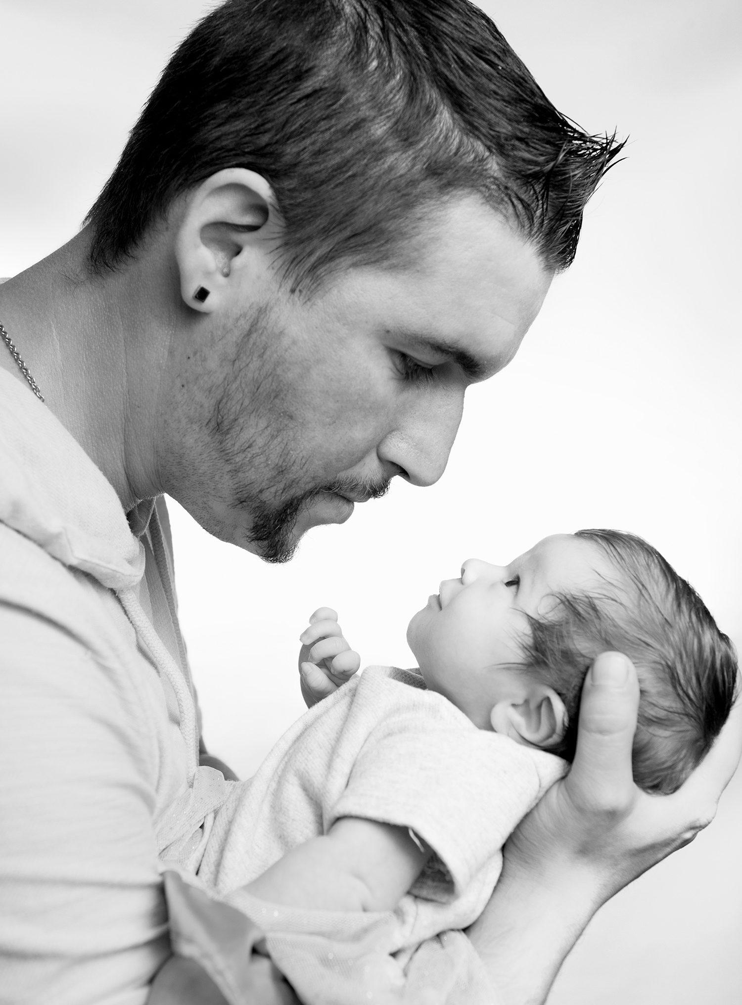 complicite dun pere qui tiens son bebe dans sa main sur fond de studio blanc