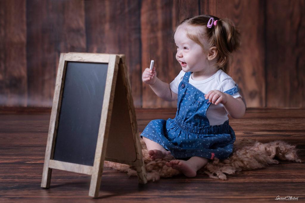 un bebe avec une craie et un tableau