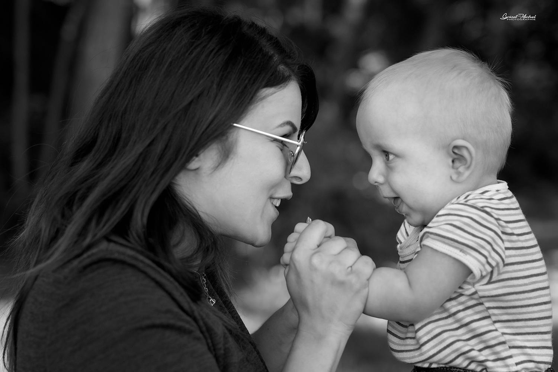 complicité entre maman et son fils qui se regard en souriant sur un banc