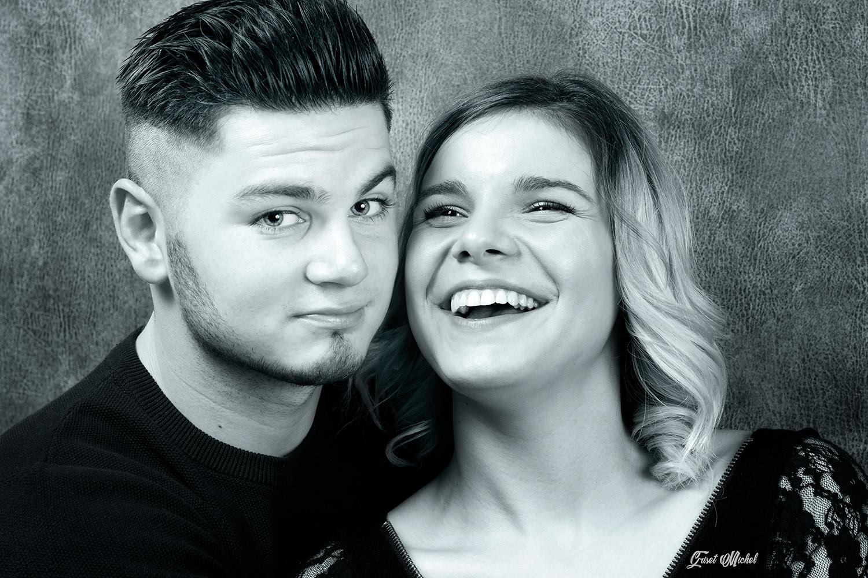 couple en studio photo un homme qui nous regard et une femme qui rigole