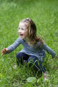 une fillette assis dans l herbe qui joue avec son pere