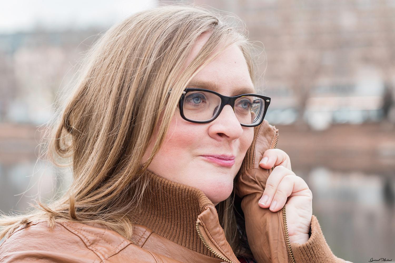 femme avec des lunettes qui rougit en souriant