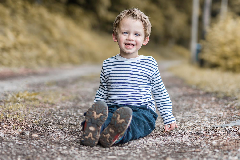 jeune garcon tres souriant assis sur un chemin de terre