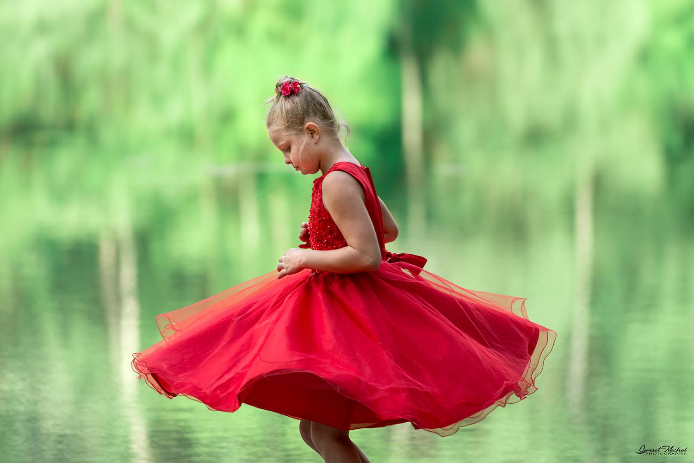 une jeune fille avec une robe rouge qui danse