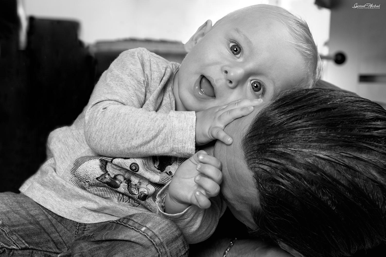 un bebe qui sourit en jouant avec son pere noir et blanc