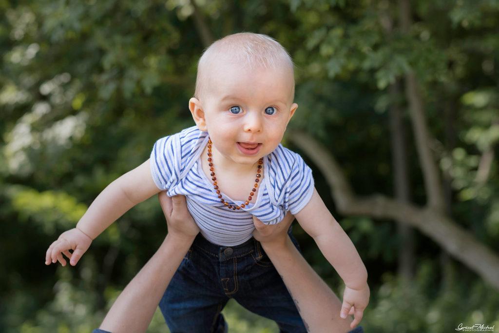 un enfant qui fait l'avion dans les bras de sa mere
