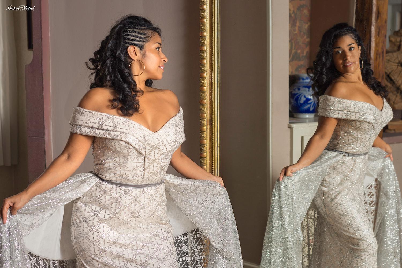 une femme en robe de mariée devant un grand miroir