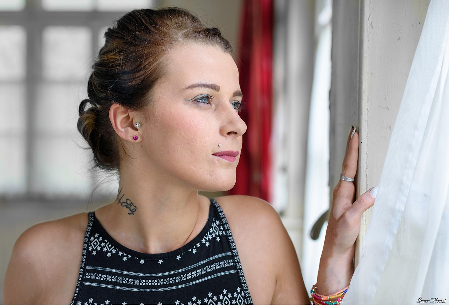 une femme avec la main posée sur un mur qui regard à la fenetre