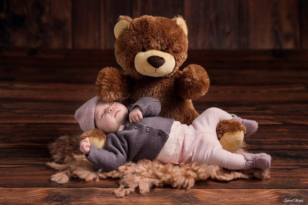 une petite fille avec un bonet en laine qui dort dans les bras de son ours en peluche