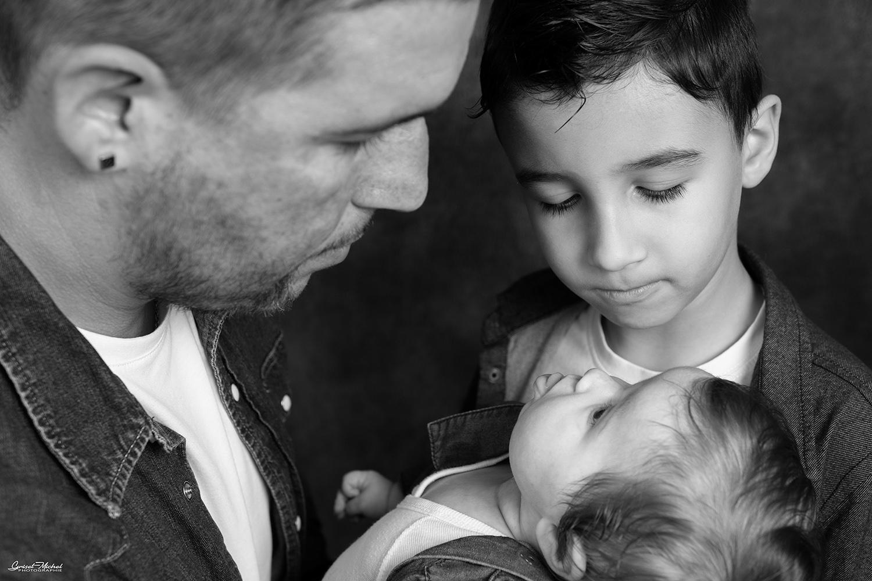 un papa avec son fil et sa fille photo en noir et blanc studio photo