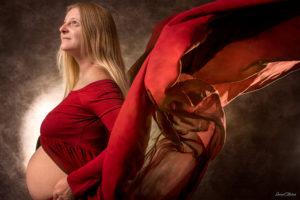 une femme enceinte dans un studio photo a selestat avec une robe rouge
