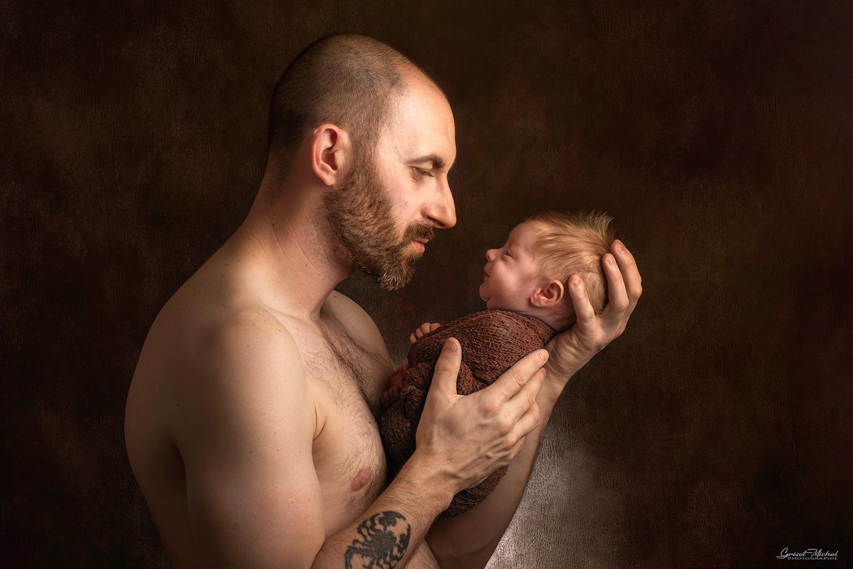 un pere tatoue qui tiens son fils dans les main en studio