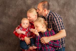 une famille au complet qui fit un bisous au petit dernier
