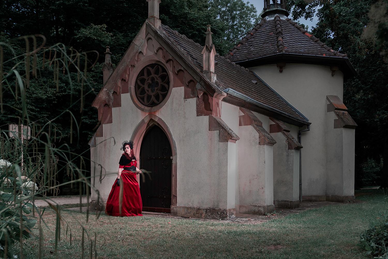 une femme avec une robe de creatrice rouge devant une eglis dans un parc a obernai