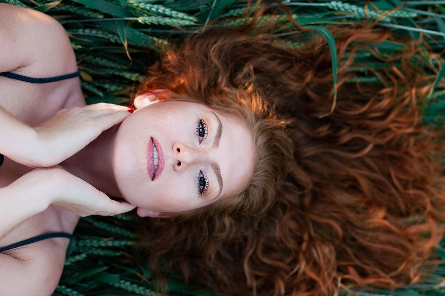une femme rousse se tiens le visage allongee dans un champs de ble
