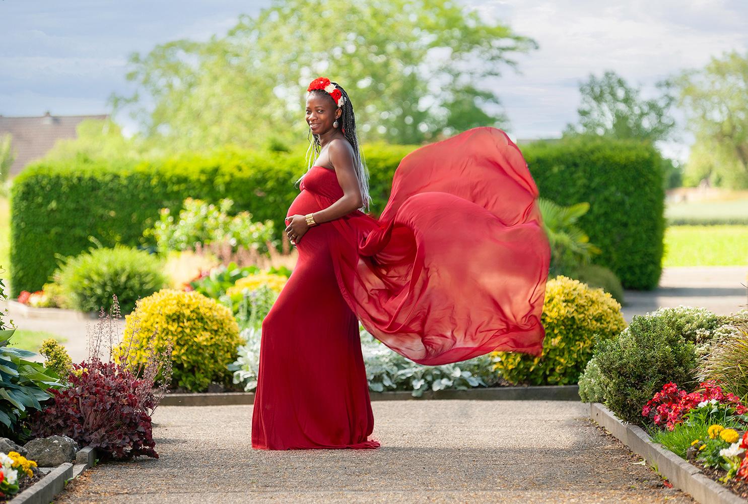 une femme enceinte avec une robe rouge qui senvole dans un jardin alsacien