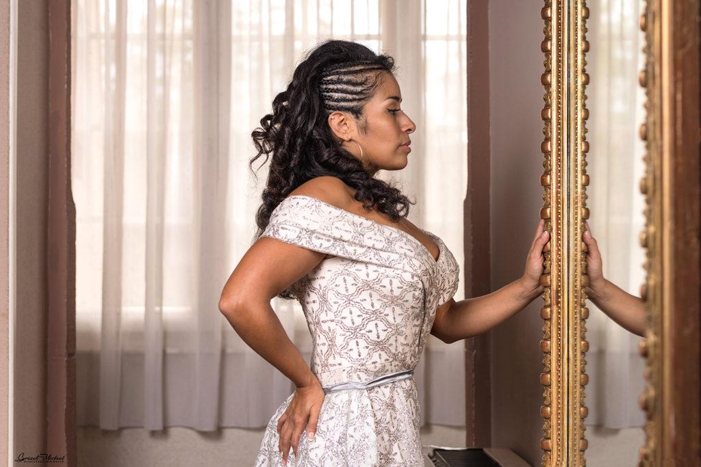 une miss en robe de haute couture qui se regard dans un miroir