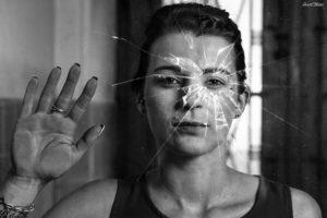 shooting portrait en urbex une femme colle a une vitre brise
