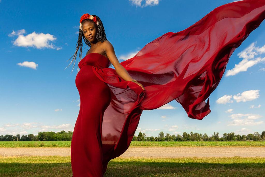 une femme enceinte avec une belle robe rouge de grossesse qui vole avec un ciel bleu