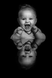 un beau bebe qui rigole avec un reflet miroir photo en noir et blanc