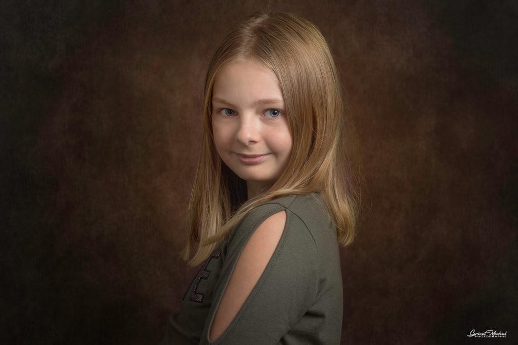 une petite fille blonde nous regarde en souriant en studio photo