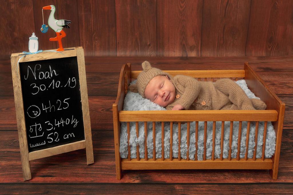 un bebe deguise en ours qui dort dans un lit avec un tableau