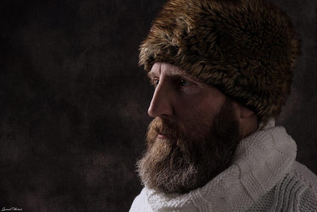 un vielle homme barbu avec un beau chapeau russe pose en studio photo