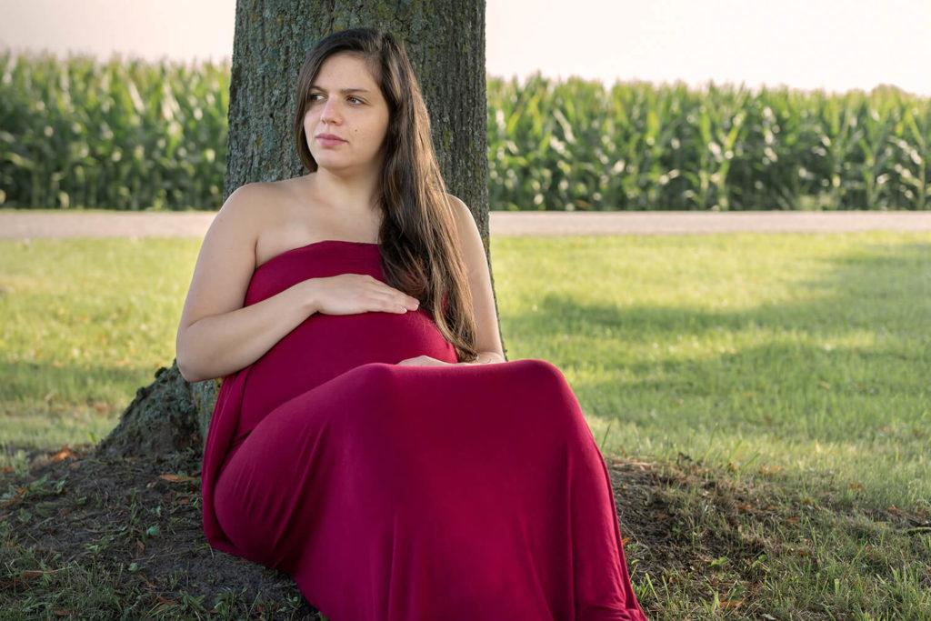 une femme enceinte se tiens paisiblement contre un arbre