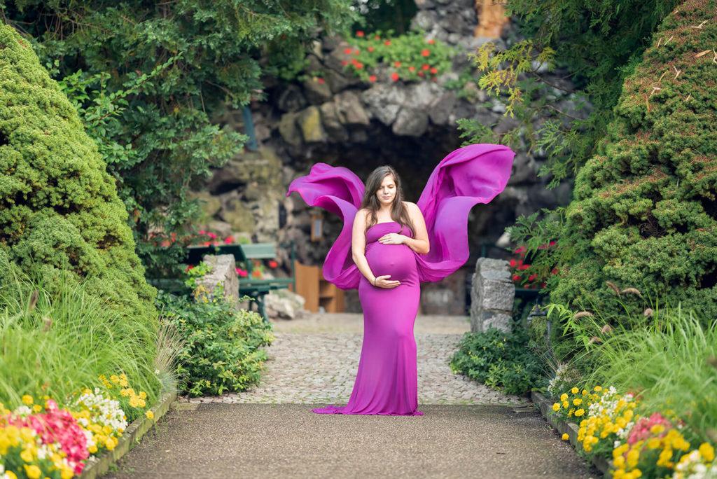 une femme enceinte avec une robe de grossesse en forme de papillon dans un jardin fleuri en alsace