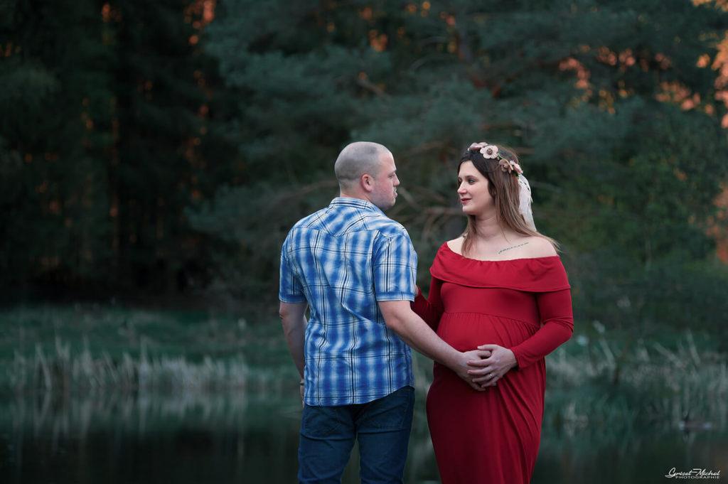 une femme enceinte regard le futur papa avec passion au bord d un etang de peche pendant une seance grossesse en famille