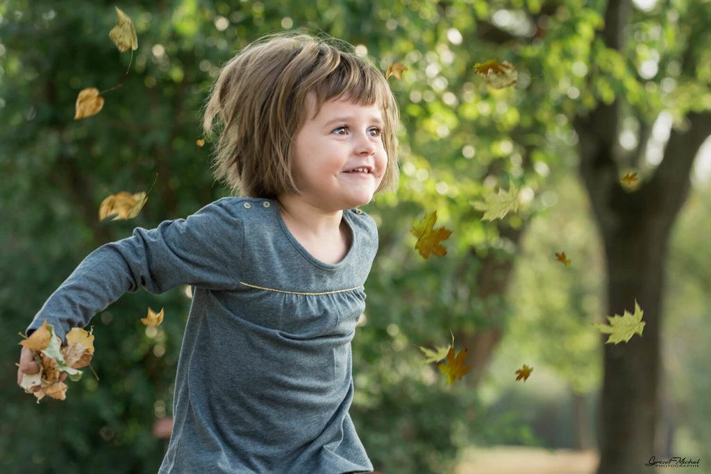 une jeune fille de 3 ans lance des feuilles en l air