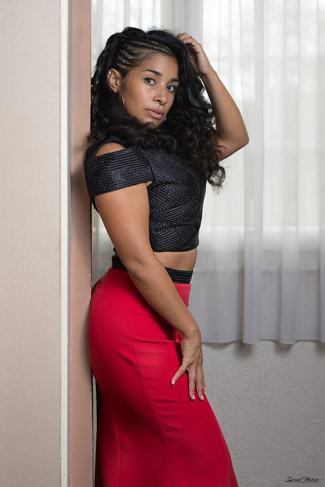 une jolie femme se tiens contre un mur avec les mains dans les cheveux